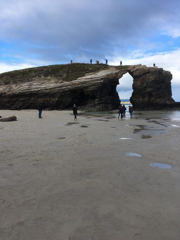 Personas encima arco playa de Las Catedrales